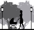 Silhouette woman walking with pram baby in park Royalty Free Stock Photo