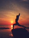 Silhouette yoga girl by the beach at sunrise doing standing tree Stock Photo