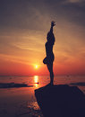 Silhouette yoga girl by the beach at sunrise doing standing tree Stock Image