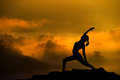 Silhouette yoga woman of doing meditation during sunrise with natural golden sunlight on mountain Royalty Free Stock Images