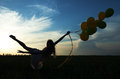 Silhouette young beautiful girl with baloons in the field Royalty Free Stock Image