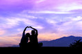 Silhouette young brother and sister made a heart shape, Beautiful sunset and sky Royalty Free Stock Photo