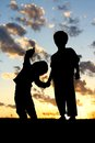 Silhouette of Young Children Holding Hands at Sunset Royalty Free Stock Photo