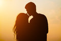 Silhouette young couple kissing over sunset background Royalty Free Stock Photo