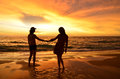 Silhouette of young couple in love on beach when sunset holding hands together as they watch the dramatic evening glow the sky Royalty Free Stock Photography