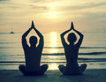 Silhouette of young couple practicing yoga on sea beach during sunset cross process photo style Stock Photography