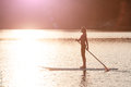 Silhouette of young girl paddle boarding at sunset01 Royalty Free Stock Photo