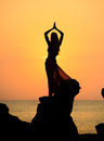 A silhouette of a young girl on rock at sunset doing yoga sunrise or wearing wrap Royalty Free Stock Photography
