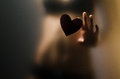 Silhouette of young girl sexual for opaque glass with paper heart in hands Stock Photo