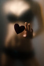 Silhouette of young girl sexual for opaque glass with paper heart in hands Stock Images