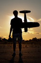 Silhouette of a young man with a model rc airplane against sunset sky Stock Image
