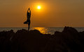Silhouette young woman lifestyle exercising vital meditate and practicing yoga on the beach at sunset Royalty Free Stock Photo