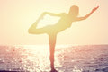 Silhouette of young woman practicing yoga on the beach near the sea, ocean at sunset Royalty Free Stock Photo