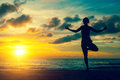 Silhouette young woman practicing yoga on the beach Royalty Free Stock Photo