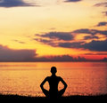 Silhouette of a young woman on a sunset meditation doing yoga exercise in the evening Royalty Free Stock Photo