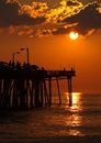 Silhouetted fishermen at sunrise on a fishing pier Stock Photo
