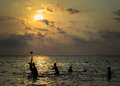 Silhouetted group of boy are playing a ball in the sea during sunset Stock Images