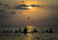 Silhouetted group of boy are playing a ball in the sea during sunset Stock Image