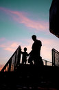 Silhouetted man and child walking down stairs in sunset Royalty Free Stock Photo