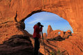 Silhouetted person photographing north window and turret arch a arches national park utah Stock Photos
