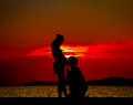 Silhouetted of young father talk to son or daugh daughter at the beach at the sunset time Royalty Free Stock Photos