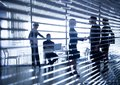 Silhouettes of business people through the blinds several businesspeople interacting background centre Stock Images