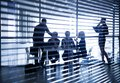 Silhouettes of business people through the blinds several businesspeople interacting background centre Royalty Free Stock Photos