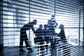 Silhouettes of business people through the blinds several businesspeople interacting background centre Royalty Free Stock Images