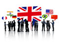 Silhouettes of business people having a discussion with each other and speech bubbles with different national flags above them Royalty Free Stock Photo