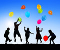 Silhouettes of cheerful children playing balloons outdoors Stock Photos