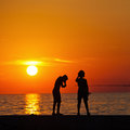 Silhouettes of children against the setting sun silhouetes angling at seacoast istria croatia Royalty Free Stock Images