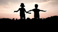 Silhouettes of children jumping off a cliff at sunset Royalty Free Stock Photo