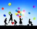 Silhouettes of children playing balloons and riding bicycle Royalty Free Stock Image