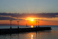 Silhouettes of dock and candelabras on summer sea at sunrise Royalty Free Stock Photography