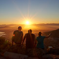 Silhouettes of friends watching a sunrise together in nature rearview three sitting on trail golden Royalty Free Stock Photos