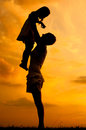 Silhouettes of happy mother and daughter at sunset Stock Images