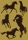 Silhouettes of horses in moving motion on a beige background animals jumping standing the front manes and tails are developing Stock Photo