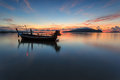 Silhouettes of longtail boat and sunrise in phuket thailand Stock Photo