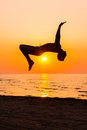 Silhouettes of a man jumping on a beach young doing jumps against sunset Royalty Free Stock Photo
