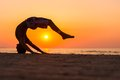 Silhouettes of a man jumping on a beach young doing jumps against sunset Royalty Free Stock Photos