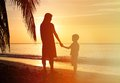 Silhouettes of mother and son holding hands at sunset sea Stock Images