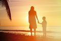 Silhouettes of mother and son holding hands at sunset sea Royalty Free Stock Photography