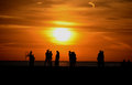 Silhouettes of people on pier silhouetted a at sunset Stock Photos