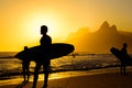 Silhouettes of surfers holding their surfboards on the background of golden sunset on Ipanema Beach , Rio de Janeiro