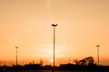 Silhouettes of three lampposts of street lighting form a perspective of a triangle against the sunset over the horizon Royalty Free Stock Photo