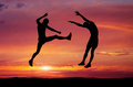 Silhouettes of two fighters on sunset fiery background battle at sunset kick in the air at the opponent s body Stock Images