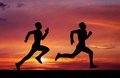 Silhouettes of two runners on sunset fiery background Stock Image