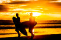Silhouettes of two surfboarders with boards walking by beach at Royalty Free Stock Photo