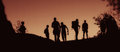 Silhouettes of walking people at dusk a group on a hill Royalty Free Stock Images
