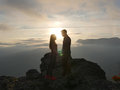 Silhouettes of young couple standing on a mountain and looking to each other on beautiful sunset background. Love of guy Royalty Free Stock Photo